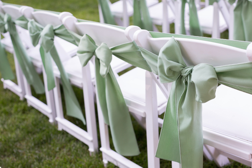 pastel green sash on white resin folding chair for wedding ceremony