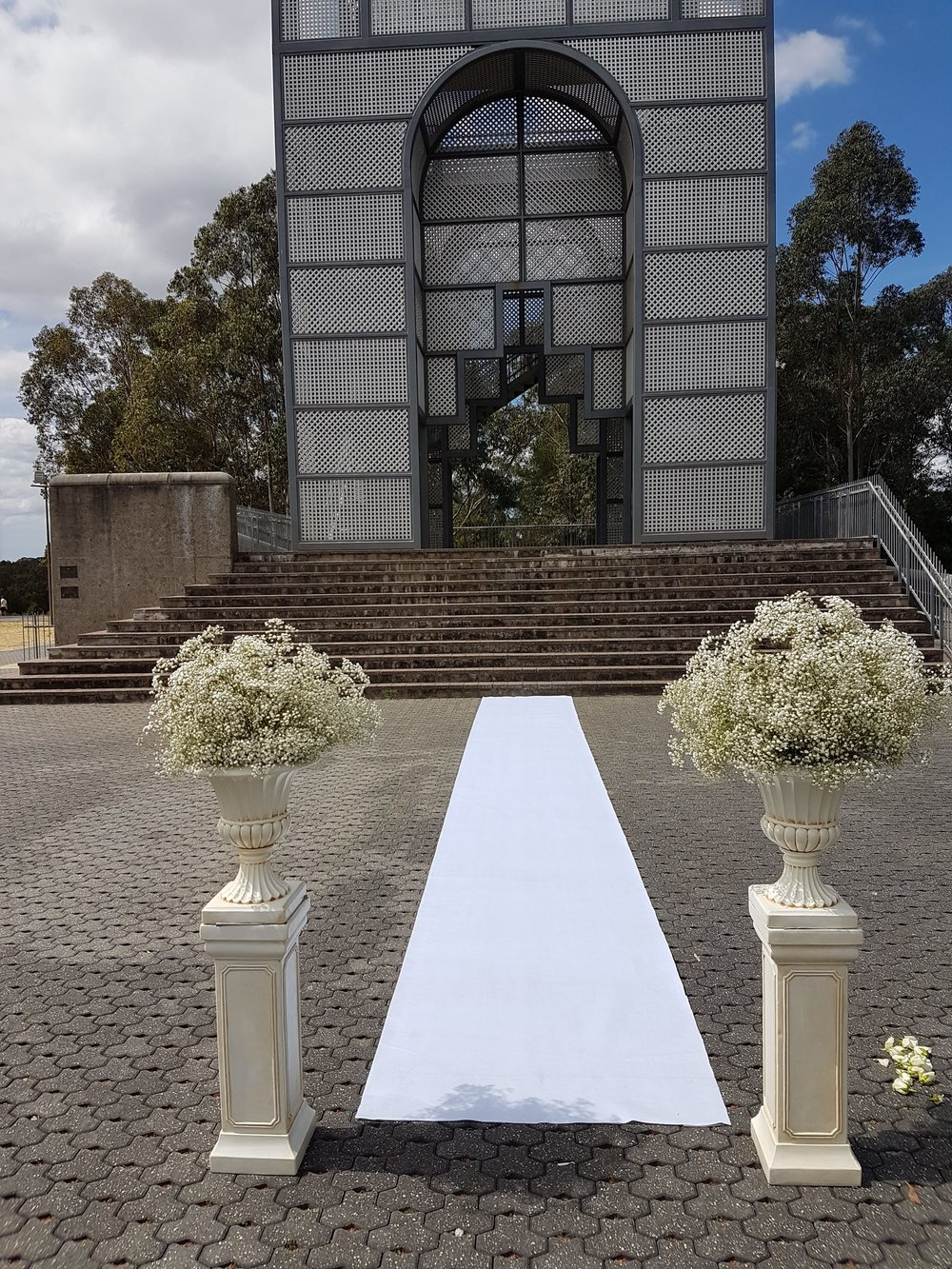 ivory plinth and urn set with babies breathe florals as entrance to ceremony aisle runner