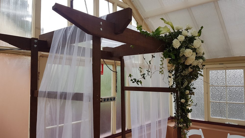 timber-wedding-ceremony-arch-with-florals.jpg