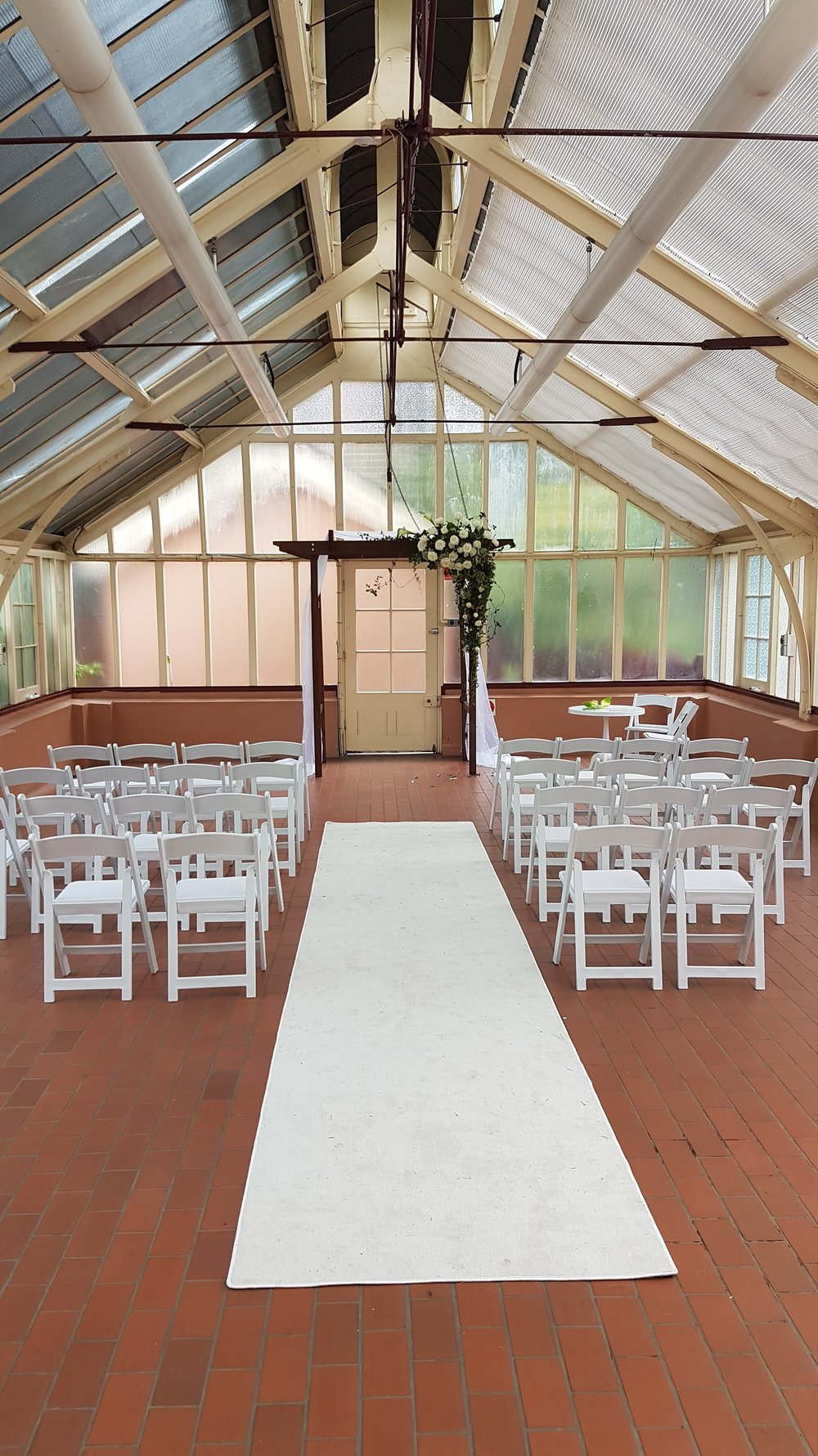 timber arbour with white styling and padded white AMERICANA folding chairs for hire
