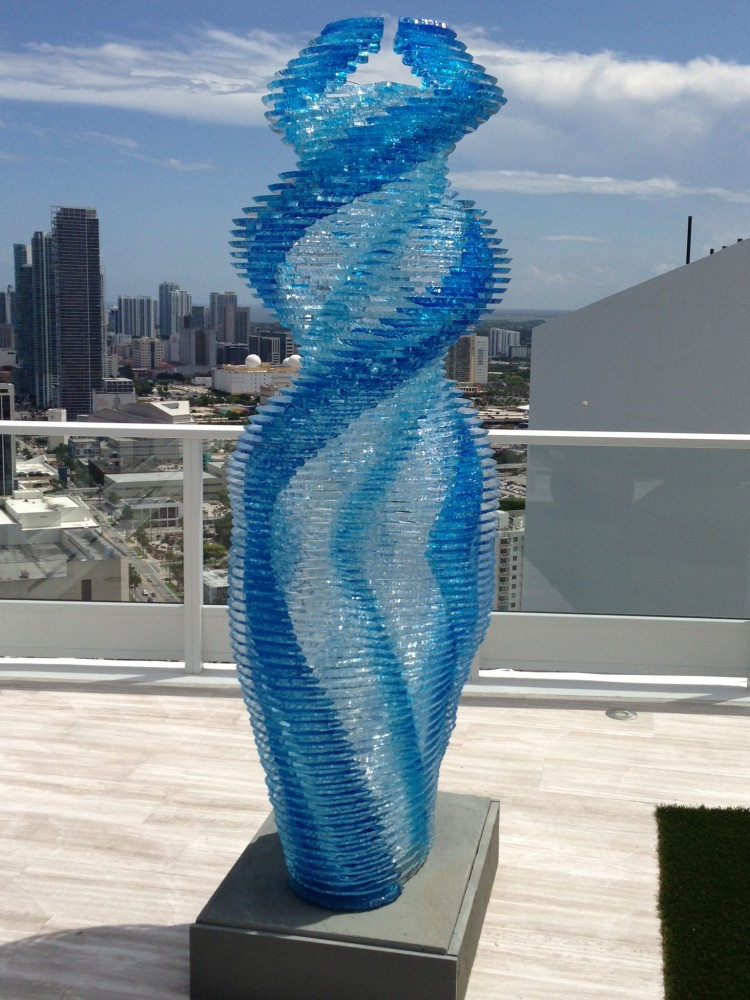 Large blue glass columnar sculpture of a woman, abstract