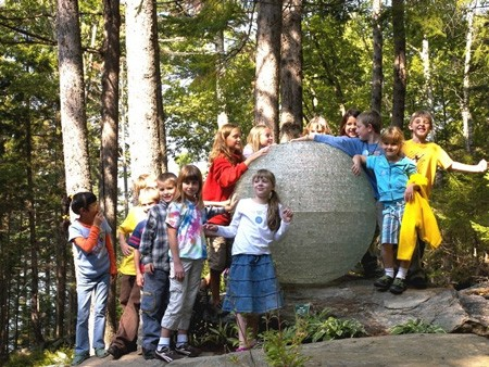 Kids and glass orb sculpture, woodland setting