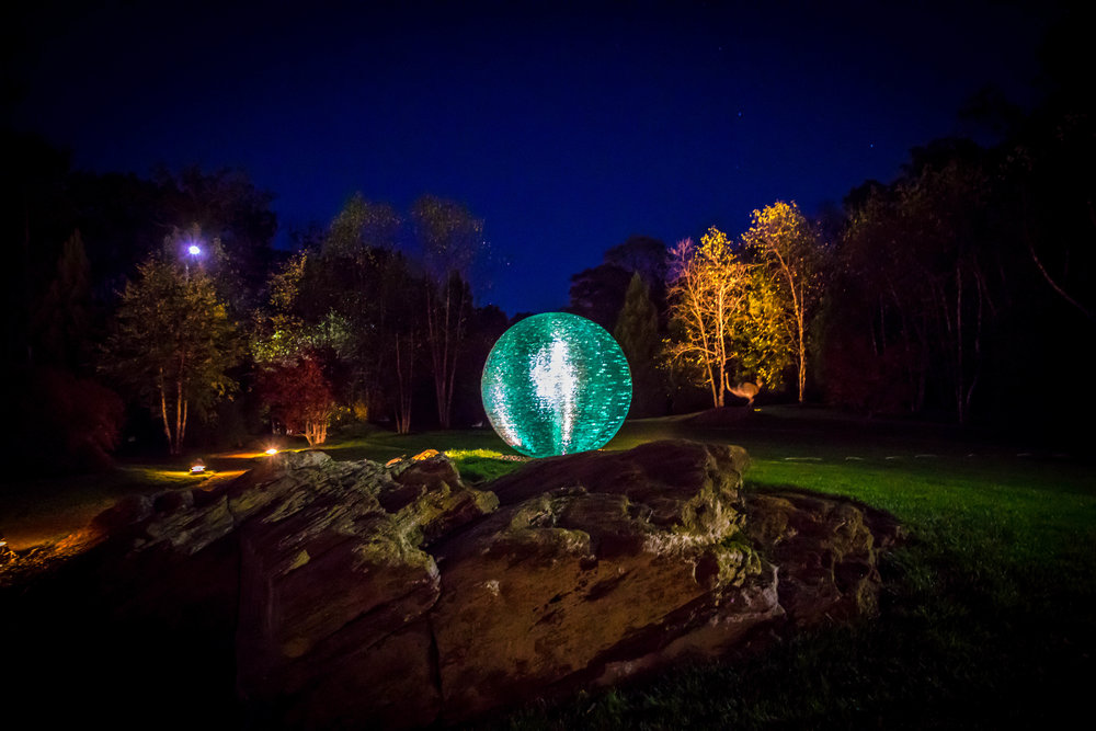 Night view of monumental green glass orb sculpture