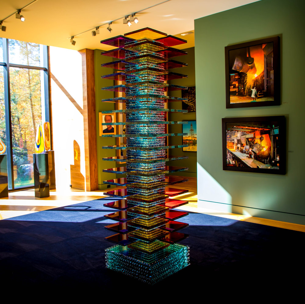 Colourful stacked glass sculpture in gallery