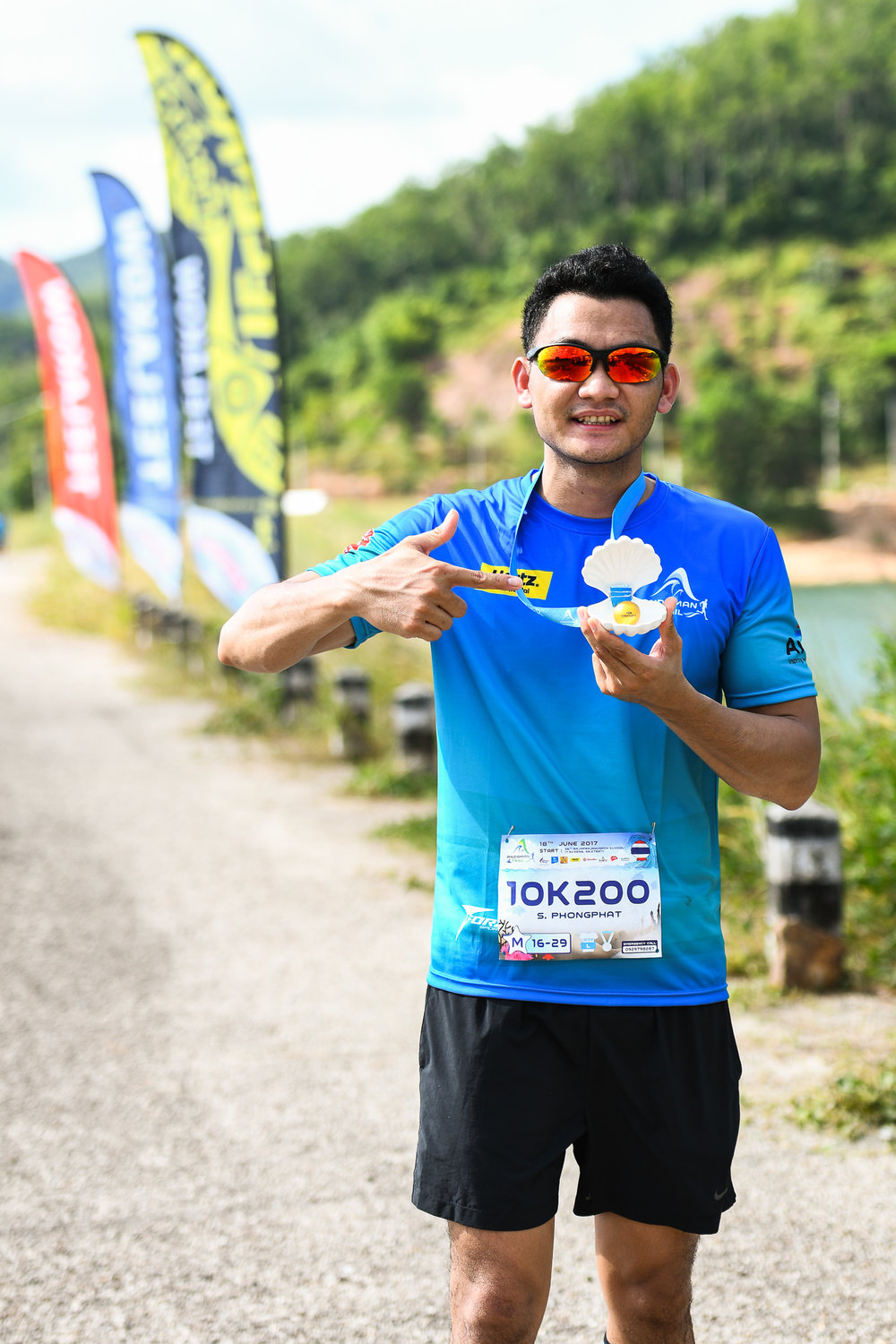 PHUKET, THAILAND - JUNE 18: Participant with his finishing medal at the Andaman Trails 2017 on June 18, 2017 at Ban Bang Niew Dam Reservoir Project, Phuket, Thailand. (Photo by: Naratip Srisupab/Thailand Photo SEALs Sports Photography)