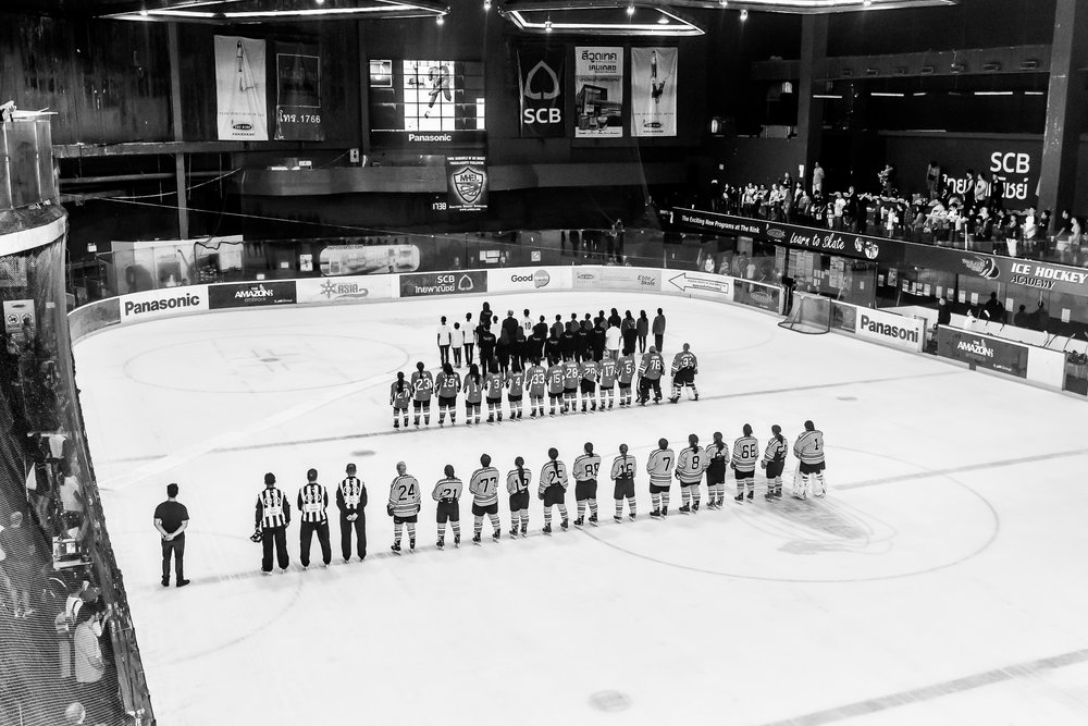 BANGKOK, THAILAND - OCTOBER 29: (This image has been converted to black and white.) SWIHC of Singapore vs Jazura of Malaysia Pre-Game Ceremony honoring the late King Bhumibol Adulyadej during JOG Land of Smiles Ice Hockey Classic 2016 Women's Samitivej Sukhumvit Final on October 29, 2016 at The Rink Central Rama IX, Bangkok, Thailand. (Photo by: Naratip Srisupab/Thailand Photo SEALs Sports Photography)