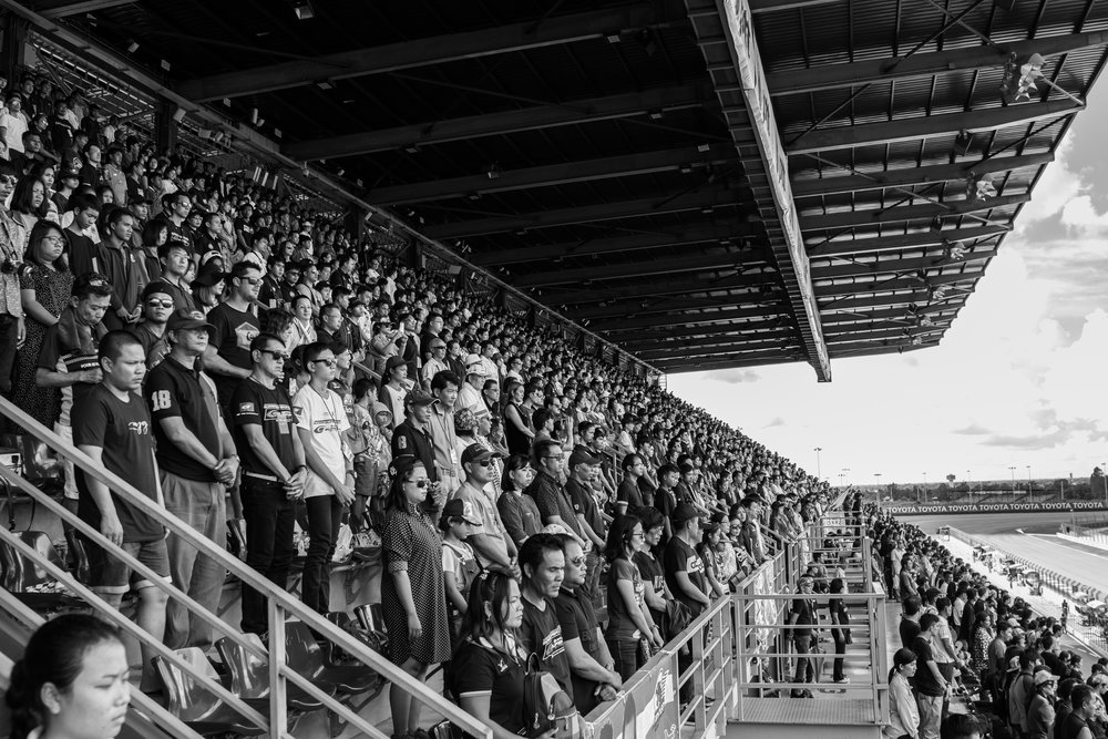 BURIRAM, THAILAND - OCTOBER 08: (This image has been converted to black and white.) Spectators in the Grandstand paying their respects to their Late King Bhumibol Adulyadej Pre-Race ceremony at the AUTOBACS Chang Super GT Round 7 Race 2017, Chang International Circuit, Buriram, Thailand on October 08, 2017. (Photo by: Naratip Srisupab/SEALs Sports Images)