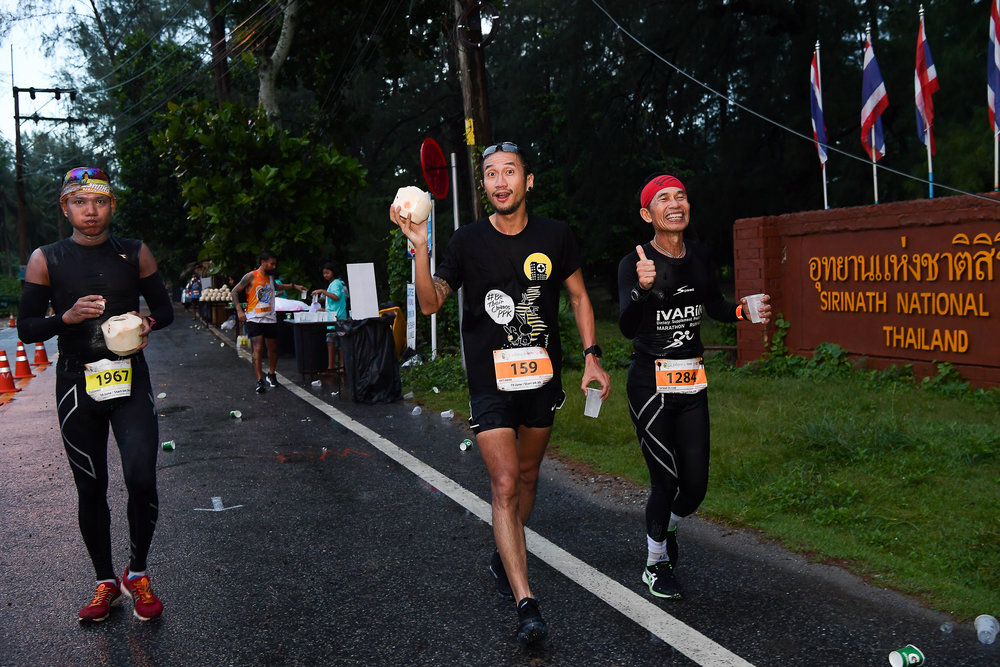 "PHUKET, THAILAND - JUNE 10: Artiwara Kongmalai ""Thoon Bodyslam"" having a fresh coconut break at the 20km marker during the 13th Laguna Phuket Marathon 2018, Phuket, Thailand on June 10, 2018. 