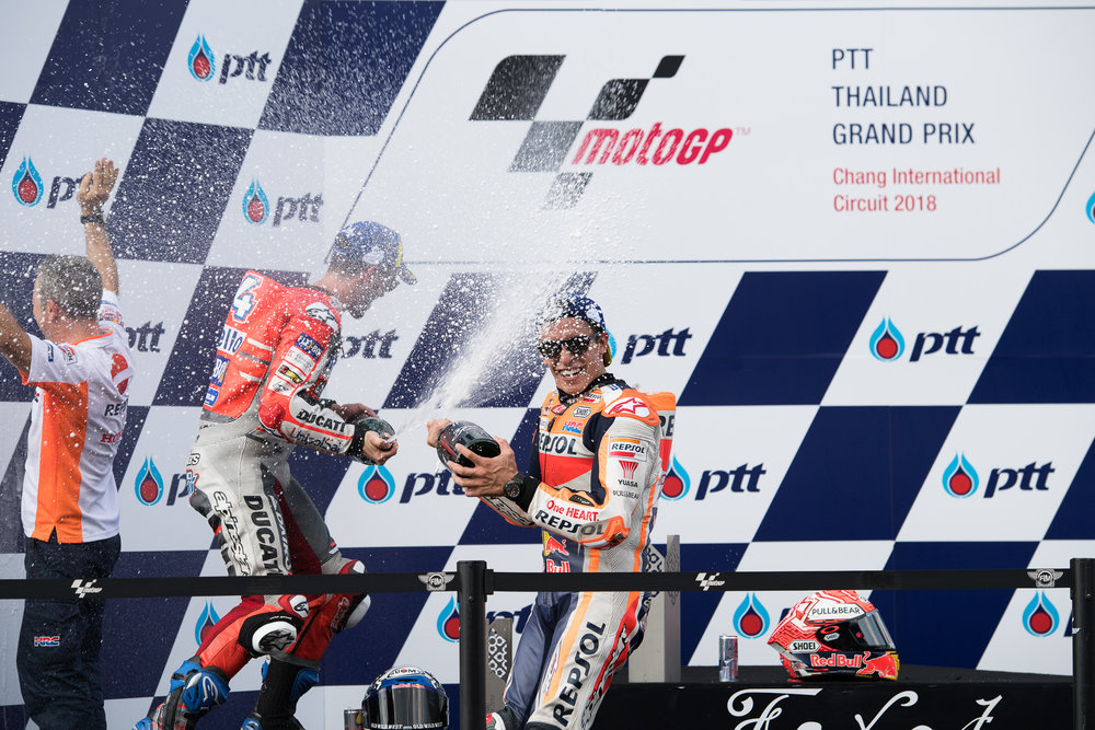 THAILAND - OCTOBER 07: Marc Marquez (93) of Spain and Repsol Honda Team and Andrea Dovizioso (04) of Italy and Ducati Team on the podium celebrating at the Inaugural MotoGP PTT Thailand Grand Prix 2018, Chang International Circuit, Thailand on October 07, 2018. 