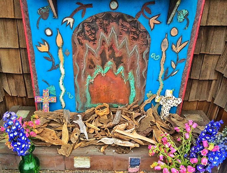 A small driftwood altar below the prayer flags