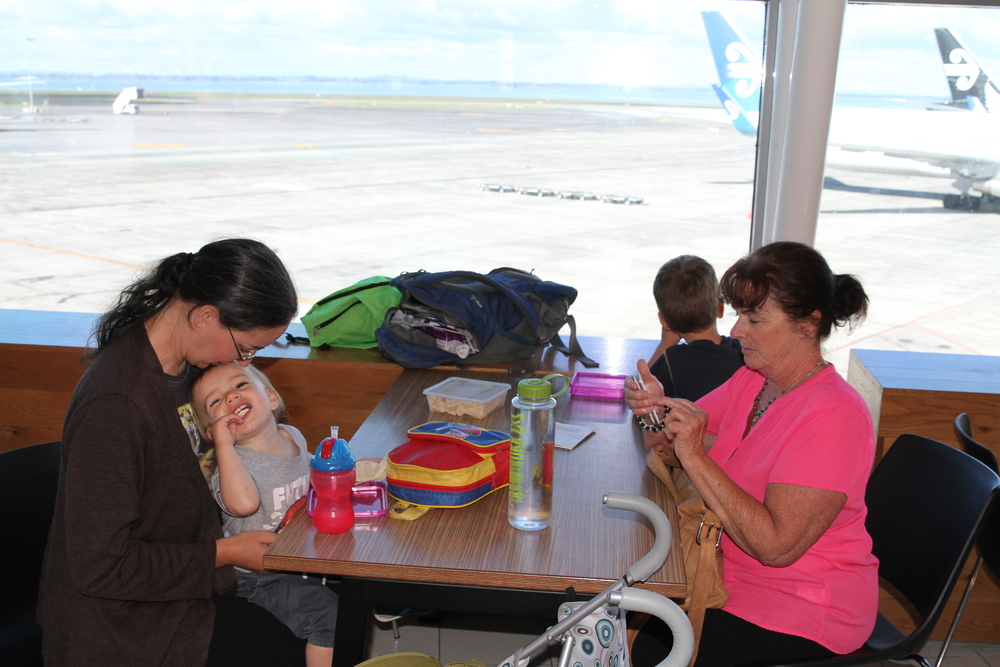 Eating lunch at Auckland Airport, with Grandma sending final goodbyes & Robin focusing on the planes.