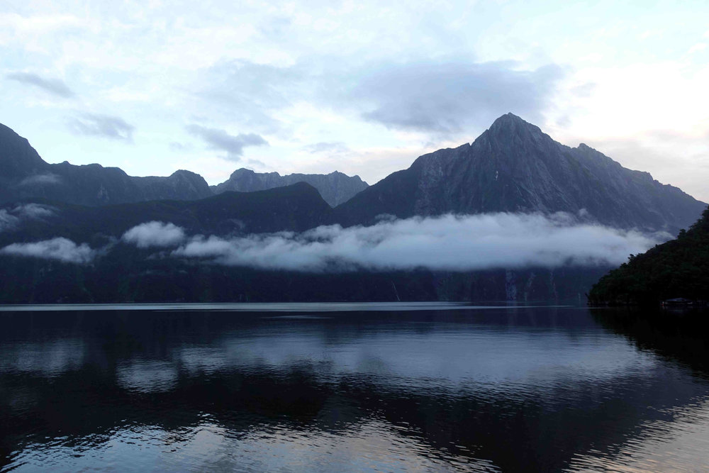 Dawn breaking on the water in Milford Sound.