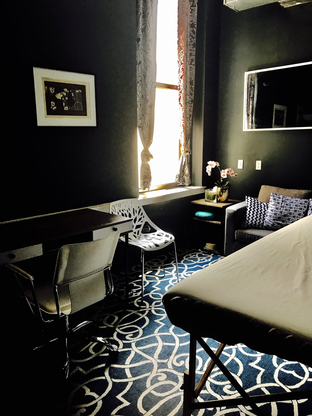 ROOM 7  This Room Features the Following:  - 14' x 10' of space  - Window with views of Broadway  - Desk, couch, and accessory chair  - Massage table can be removed from the room for use as a therapy suit