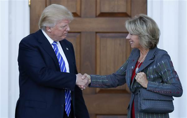 President-elect Donald Trump and Betsy DeVos shake hands at Trump National Golf Club Bedminster clubhouse in Bedminster, N.J., Saturday, Nov. 19, 2016. PHOTO CREDIT: Carolyn Kaster / AP