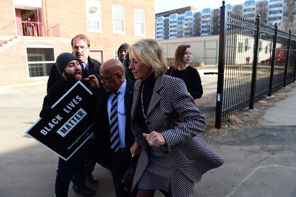 Protesters block Education Secretary Betsy DeVos and clash with her security detail as she arrives at Jefferson Middle School Academy in Washington. (Don Baxter/Media Images International)