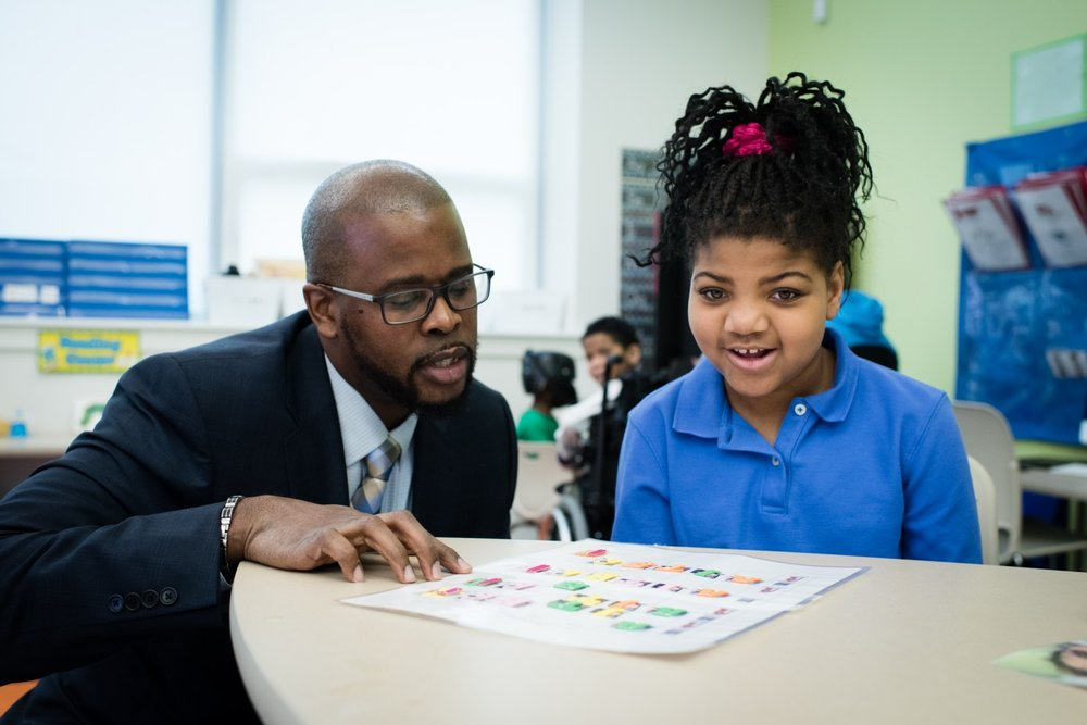 Antwan Wilson, chancellor of D.C. Public Schools, talks to Kiara Jones, 8, right, a visually impaired third-grader at River Terrace Education Campus. Photo Credit: Sarah L. Voisin/The Washington Post
