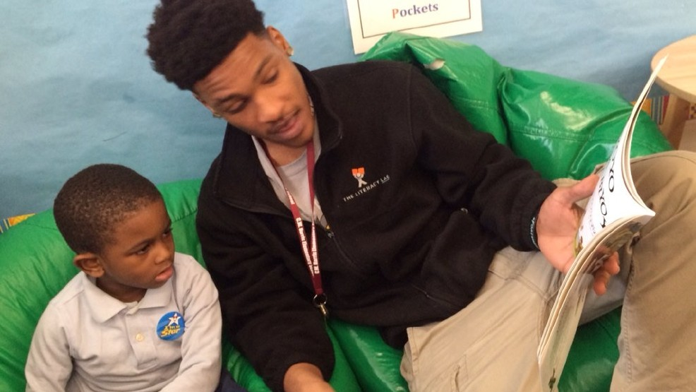 D.C. high school graduate Chenier Beale works as a tutor in Pre-K class and reads to a student, Monday, March 20, 2017 (Kellye Lynn/ABC7 )