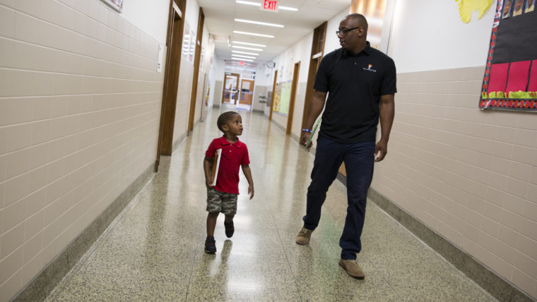 Torren Cooper, a Leading Men Fellow, walks with Kree Reid, 3, to a spot in the hallway of Turner Elementary School where they will work on literacy skills. Photo Credit: Tyrone Turner / WAMU