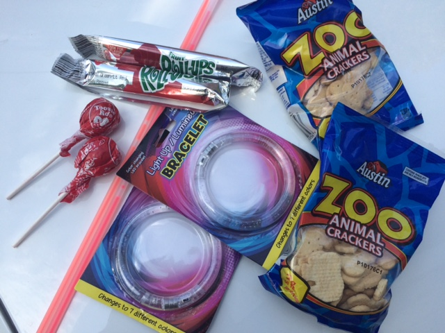 My DIY circus fun kit: Fruit Roll-Ups, Tootsie Pops, animal crackers, glow necklaces and $1 light-up multi-colored bracelets.