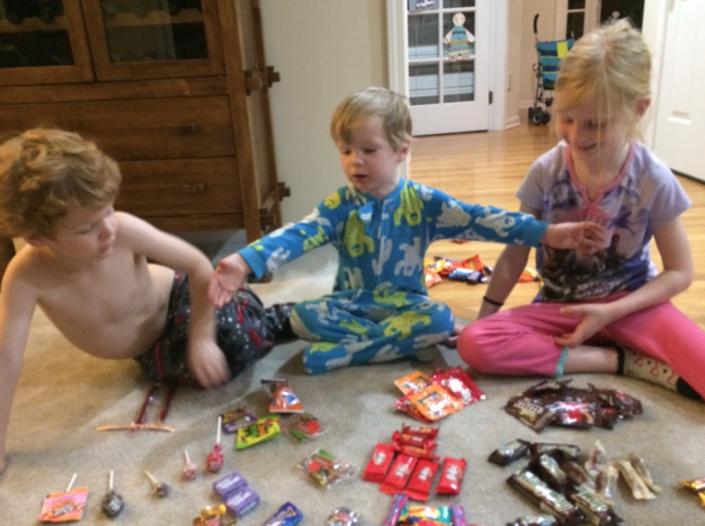 "Big brother and big sister trying to ""help"" the little man decide what to do with all his candy."