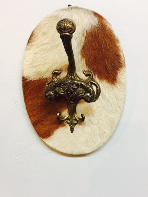 "Just arrived! Vintage brass hat & coat hook on cow hide! 13"" in height. 2195 Calder Ave, Beaumont Tx, 77701, 409.835.3080"