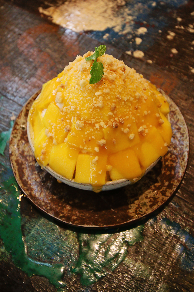 Deconstructed mango cheesecake. Juicy mangos covered in sauce with biscuit crumb on top of a mixture of cheesecake chunks and white snow. The best yet!