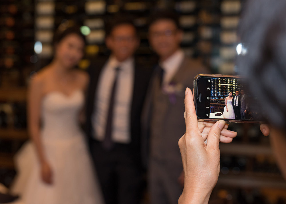 Bride, Groom and friend pose for i-Phone Wedding Reception Photo