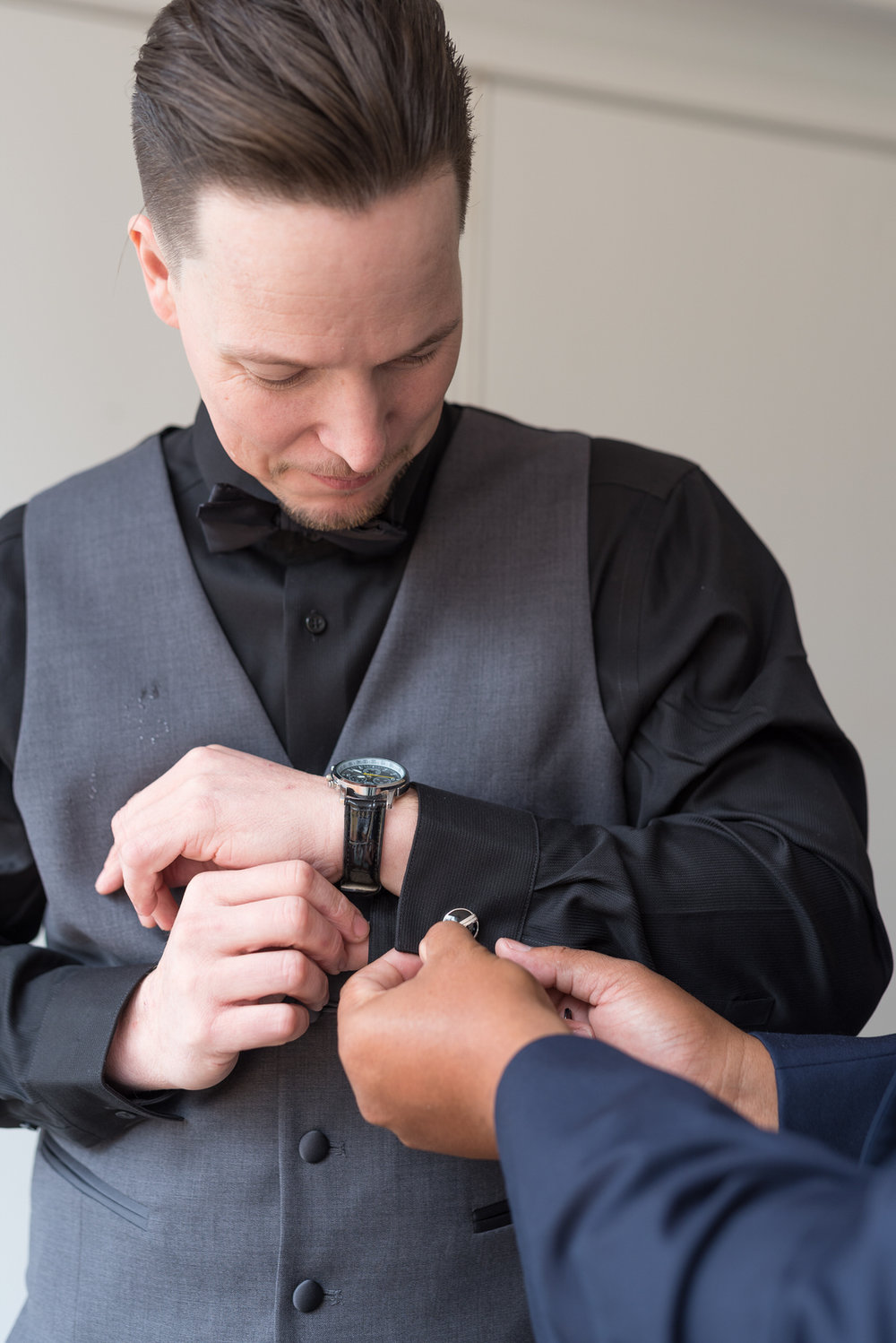 clean cute Groom getting help with cufflinks from his Best Man