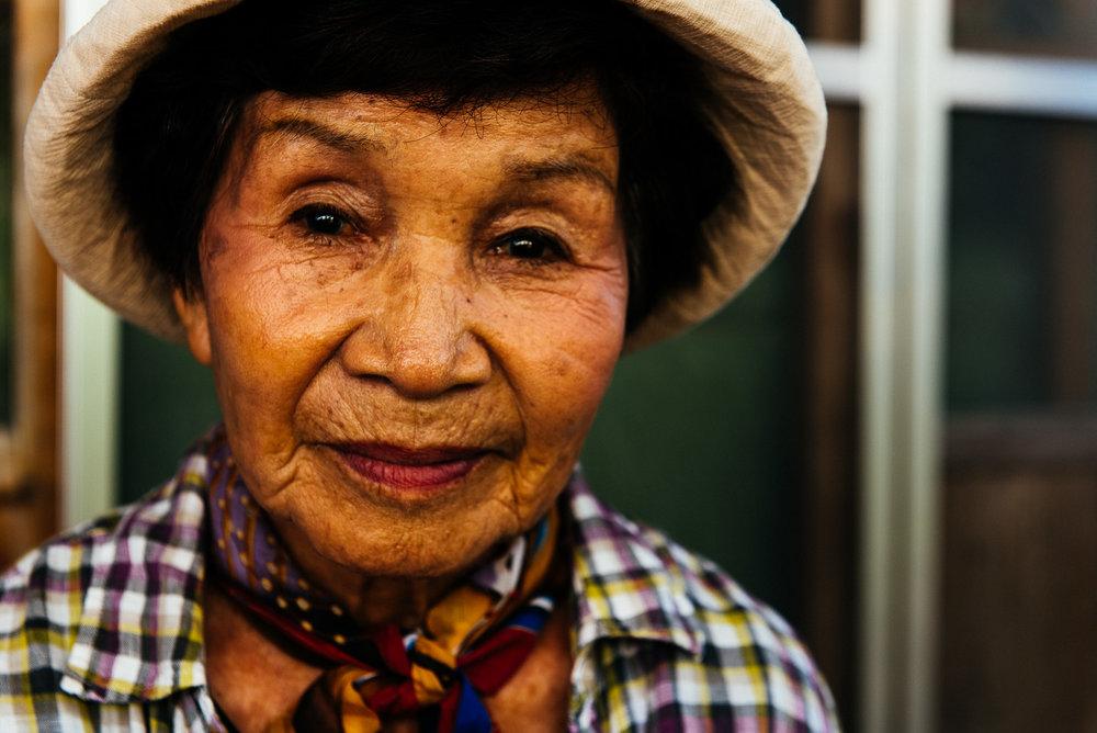 Kikue Okushima a 89 ans. Cette petite dame super active travaille bénévolement au bureau de la ville d'Ogimi, célèbre pour son nombre important de centenaires. Elle adore cuisiner, jardiner, chanter, rire. Les petits plaisirs de la vie sont importants pour elle. Elle ne se rend jamais au supermarché. Elle ne consomme que des produits locaux. Il lui arrive même aussi de donner des conférences sur sa manière de vivre et sur les secrets de la longévité.    Kikue Okushima is 89. This little, very active lady works as a volunteer at the Ogimi town office. Ogimi is famous for the large number of centenarians who live there. She loves cooking, gardening, singing, and laughing. She never goes to the supermarket; she only buys local products. She even happens to give lectures on her lifestyle and the secrets of longevity.