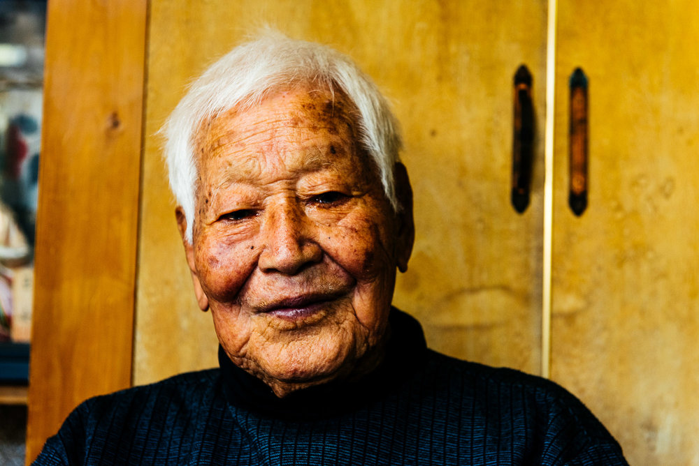 Shinpuku Tamaki a 100 ans. Il a été agriculteur toute sa vie et se déplace encore aux champs tous les jours. Il se lève tous les jours vers 6-7h. Il va marcher très doucement. Il prend un petit déjeuner normal vers 8h. Il ne consomme que des produits locaux. Son secret ? Rien de spécial selon lui. Quand il était jeune, il aimait pêcher et escalader les montagnes. Aujourd'hui, il pratique le gateball avec ses amis. Il va se coucher généralement vers 21h. Il a eu une vie simple, sans maladie, sans stress particulier. Shinpuku Tamaki is 100. He has been a farmer all his life and still goes to the fields every day. He wakes up at about 6 or 7 a.m. and has a slow walk. Then, around 8 o'clock, he has a normal breakfast. He only eats local products. What's his secret? Nothing special, according to him. When he was young, he loved fishing and climbing mountains. Today, he plays gateball with his friends. He usually goes to bed at 9 p.m. He has had a simple life, without illness, without any particular stress.