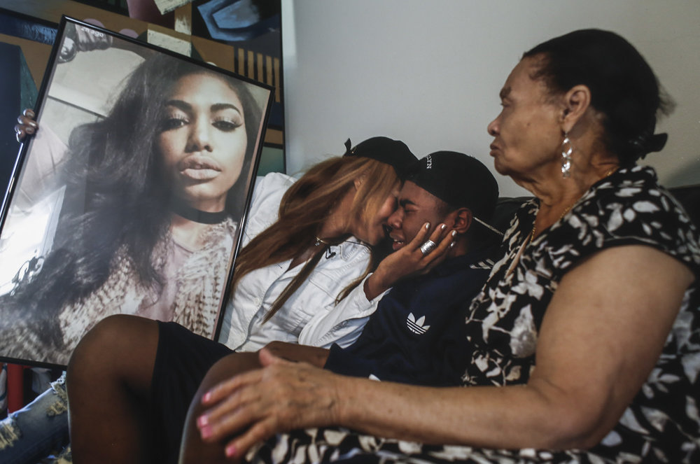 Mercedes Concepcion holds a frame of her daughter, Ashley Perdomo, while grieving with her son, Bryant Perdomo, 19, and mother, Vicky Guillen, at their home in Tampa, Fla., on Oct. 13, 2016. Ashley Perdomo, 17, was killed in a hit-and-run while trying to cross Hillsborough Ave after leaving work. Authorities are still looking for a suspect. The family is calling for anyone who has information about the driver to come forward. She was a senior at Hillsborough High School.