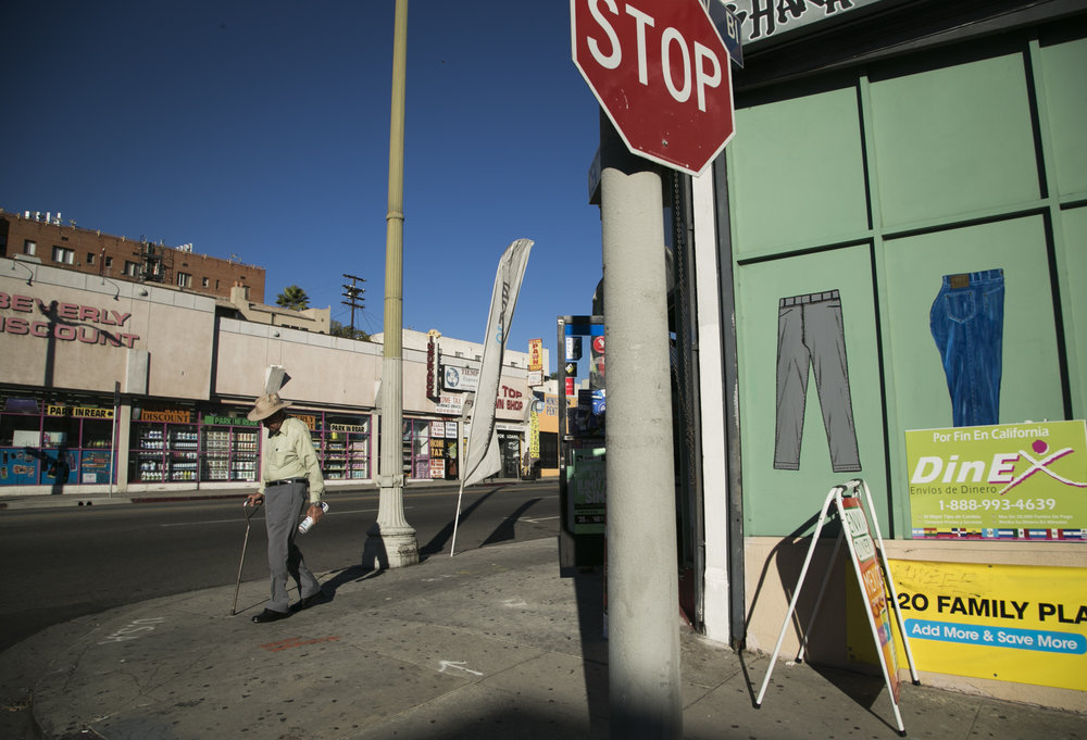 A bystander walks along the corner of Mariposa Street and Beverly Boulevard in Koreatown. The street shows a variety of Salvadorian owned businesses that cater to the Spanish speaking community including remittance services, a mobile store that provides pre-paid phone cards and an El Salvadorian market. The 1980s marked Koreatown's dramatic transformation to becoming a multicultural space. During this period, a large influx of Central Americans, Mexican Americans and Bengali Americans began to move in to the area.