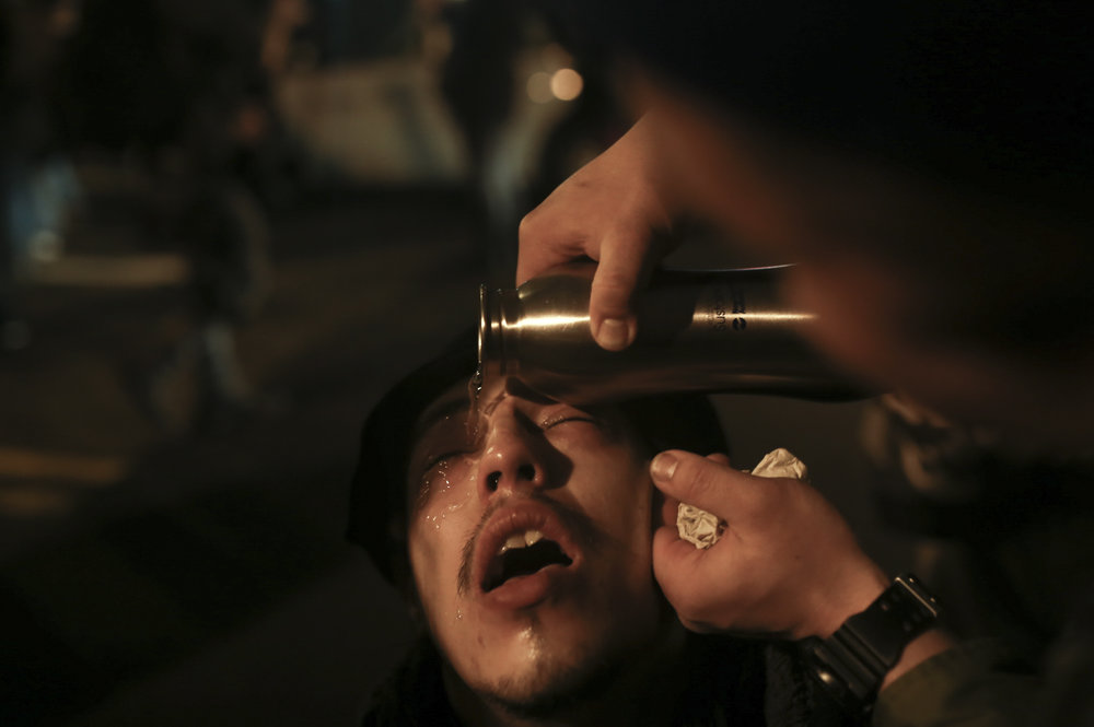 A protestor reacts as a friend  rinses his eyes. Riot officers used pepper spray on protestors on 11th Street and M Street in downtown Washington D.C. following President Donald Trump's inauguration on January 20, 2017