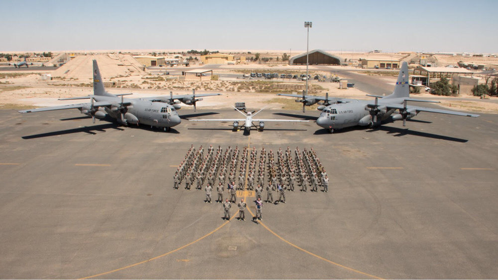 Andrew Kavanah and his crew in Kuwait along with two of the planes he services (C-130s).