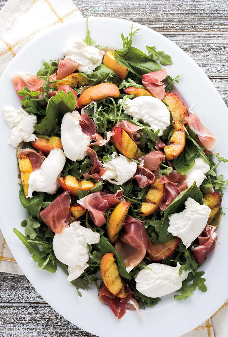 Sweet grilled peaches with creamy burrata cheese, prosciutto and basil over a bed of arugula make the perfect summer salad.