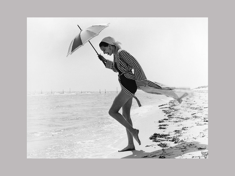 "George Oddner   ""Vårdopp, Falsterbo"",  1952 C-print 80 x 100 cm  ""What a great eye he had. This is actually from a fashion shoot, but Oddner had the ability to capture all details and appeal to our common concept of good times by the beach. Falsterbo in the south is Sweden's own Saint Tropez. Look how the stripes in her robe play with the lines of her legs and how the sea disappears. And on top of that: her tongue sticking out and revealing her doubtfulness to jump in."""