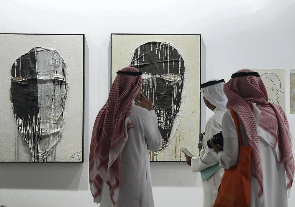 Photo: Visitors study the works on display during Art Dubai at Madinat Jumeirah. Pawan Singh / The National.