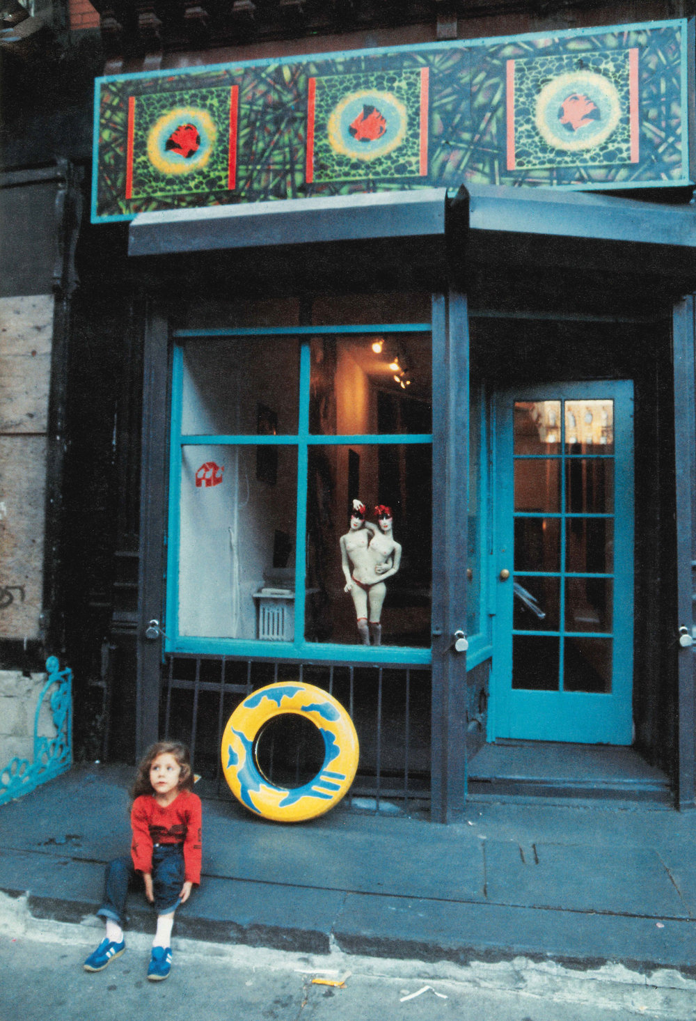Outside Cilvilian Warfare in 1983. Photograph published in the catalogue to the Neo York exhibition, 1984. The store front sign by David Wojnarowicz.