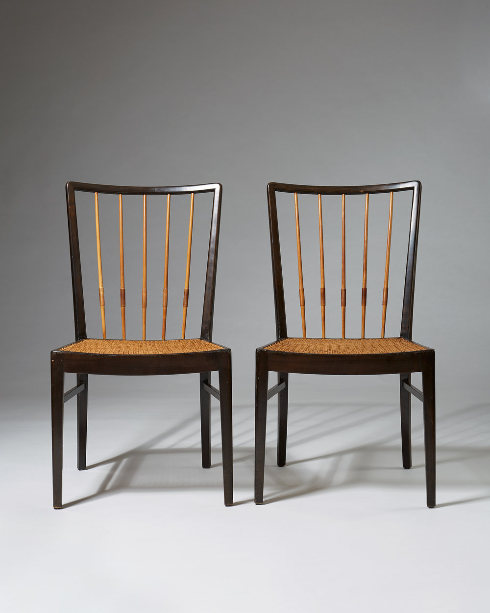 Unknown  Set of twelve chairs Sweden, 1950's Mahogany, lacquered mahogany and cane. 62 x 50 x 49 cm Seat: 44 cm