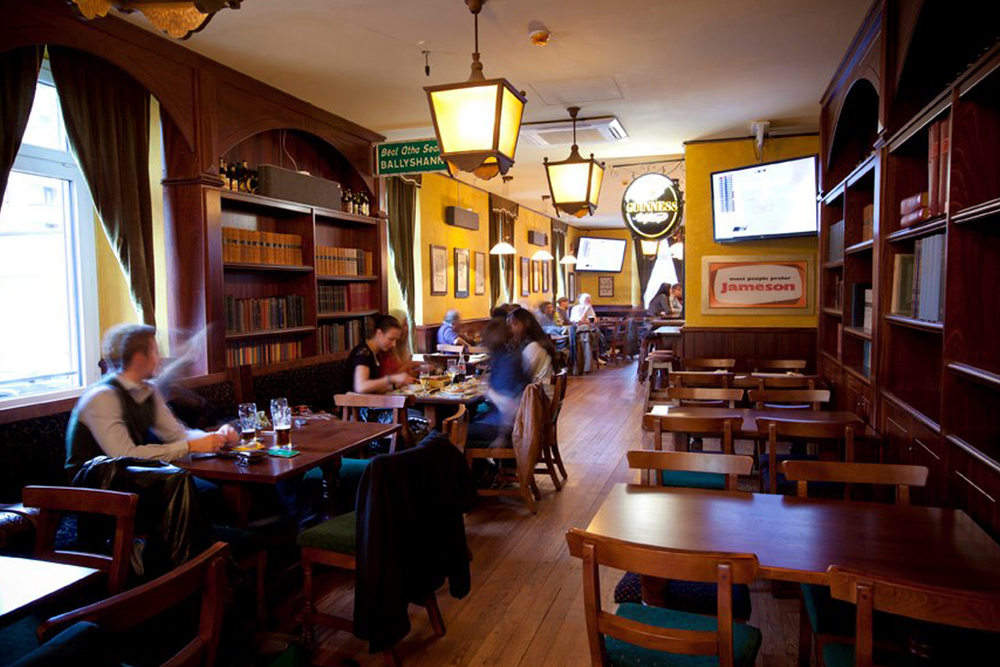 The Trinity Irish Pub Design Interior - yellow walls with soft lighting and wooden furniture.