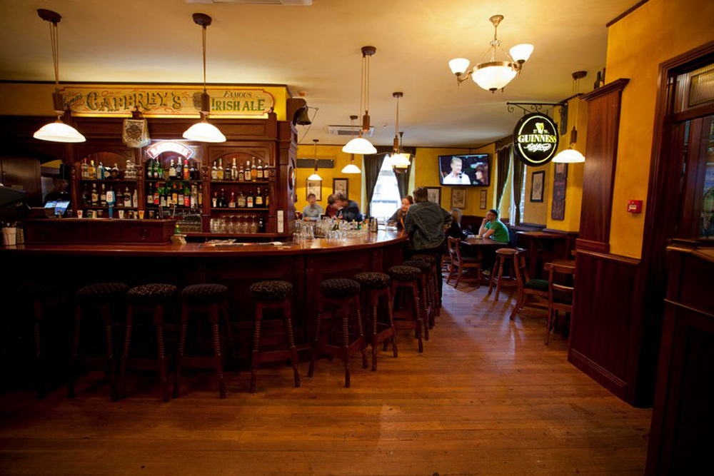 The Trinity Irish pub design interior - pictured is the curved wooden bar with yellow walls and soft yellow lighting.