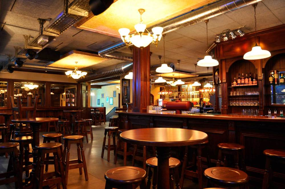 Peggy O'Neil's Irish pub design - interior view of wooden bar and high wooden tables with wooden stools
