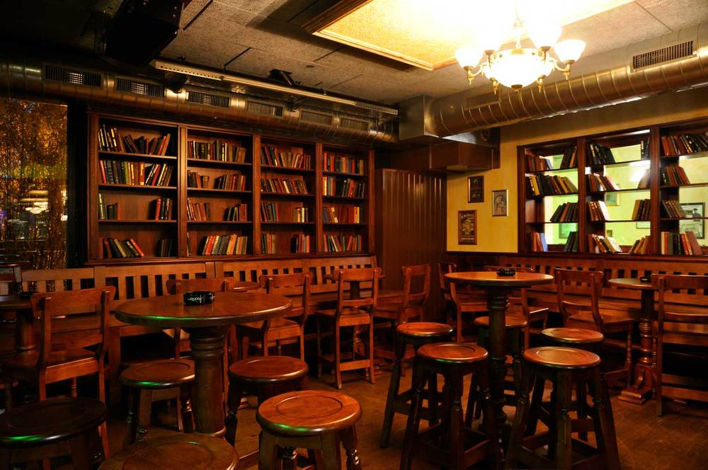 Peggy O'Neil's authentic Irish pub design - interior seating, low wooden tables and wooden chairs with books on wooden shelving