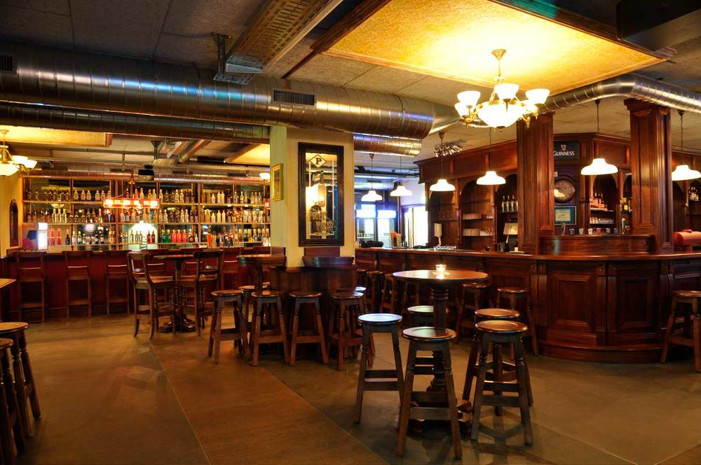 Peggy O'Neil's authentic Irish pub design - interior seating with high wooden tables and stools