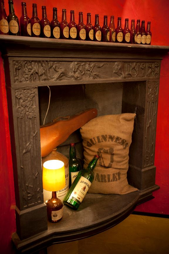 Trinity Irish Pub design - stone fireplace by Guiness designers with Jameson bottles inside and Guiness bottles on the mantlepiece