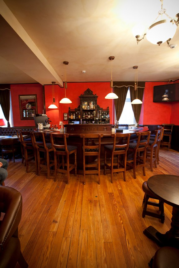 Trinity Irish Pub Design - Interior view curved wooden bar and stools with red walls