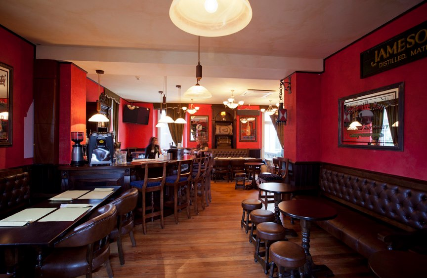Trinity Irish Pub Design - interior view, low wooden tables and stools with leather upholstered sofas and red walls