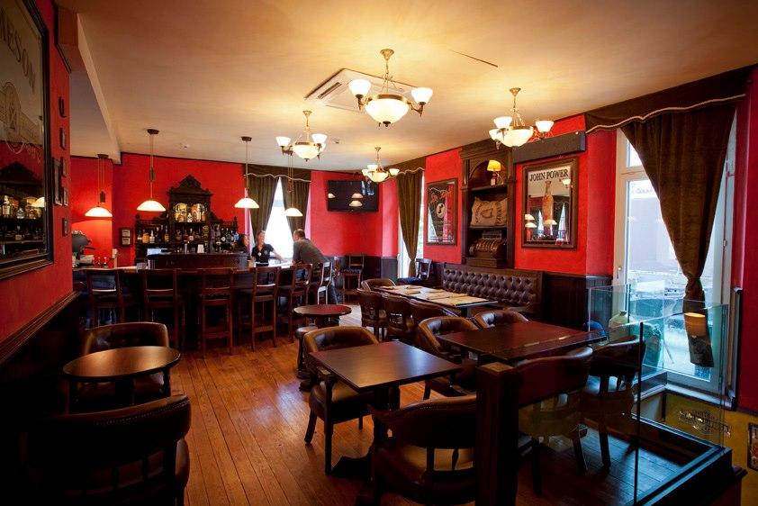 Trinity Irish pub design - interior view dining area with low wooden square tables and chairs, red walls and heavy red velvet curtains