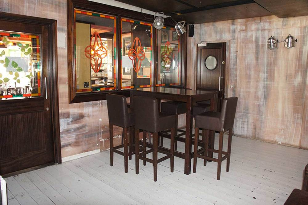 Duffy O'Toole's authentic Irish pub design - interior view of pub corner with high table and stools. Mirrors adorned with celtic emblems.