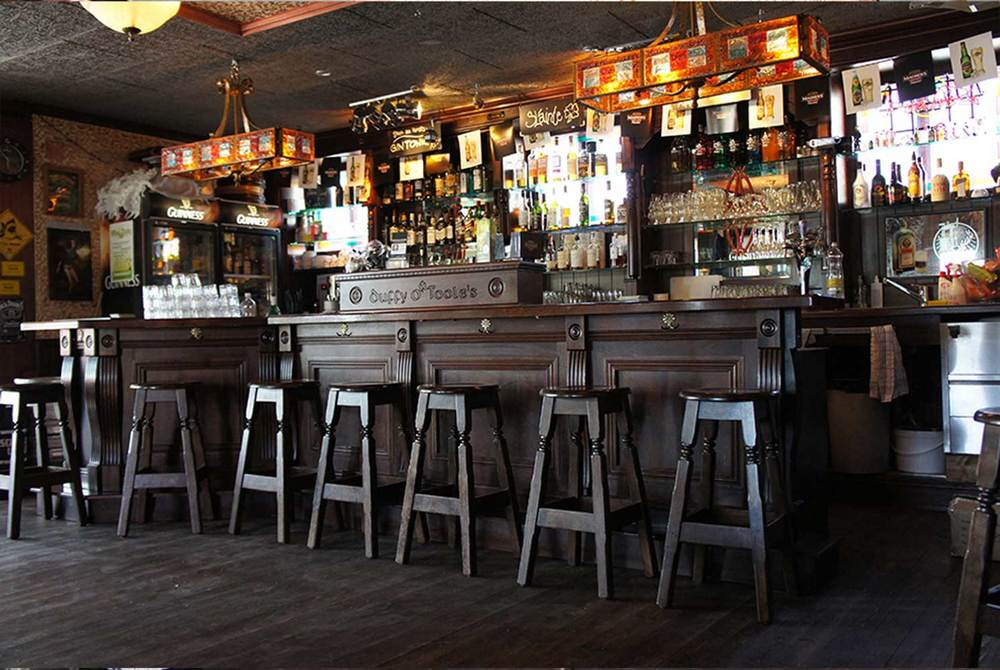 Duffy O'Toole's authentic Irish pub design - interior view of dark wood bar with 'Duffy O'Toole's' engraved into wood and high wooden stools lined up.